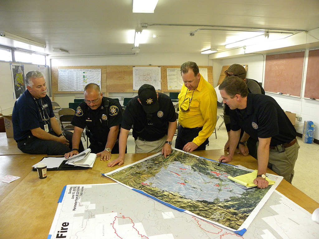 Larimer County Emergency Services head Bill Nelson (left) meets with Sheriff's Office staff during a fire fighting planning session